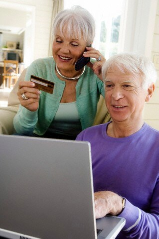 Senior man using laptop computer, senior woman phoning, holding credit card --- Image by © A. Chederros/Onoky/Corbis