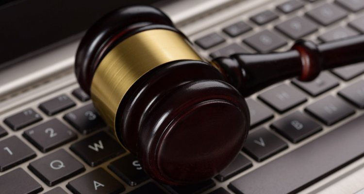 Gavel laying on top of a laptop keypad
