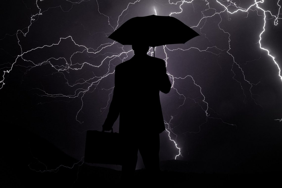 businessman holding an umbrella during the storm with lightning