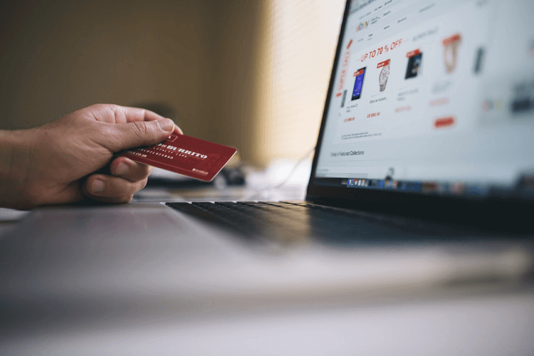 a person in front of a laptop holding a credit card