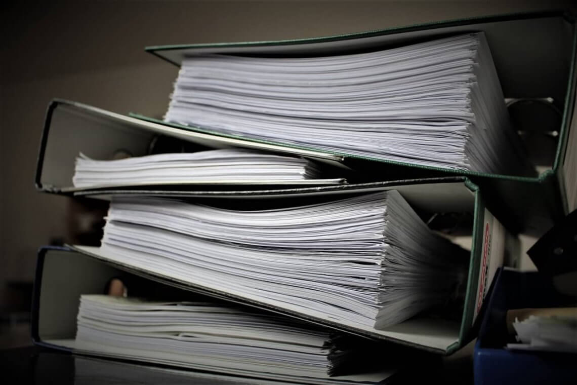 a stack of old binders filled with documents