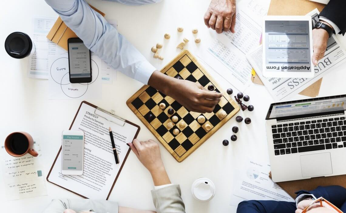 aerial view of a desk with business papers and people playing chess