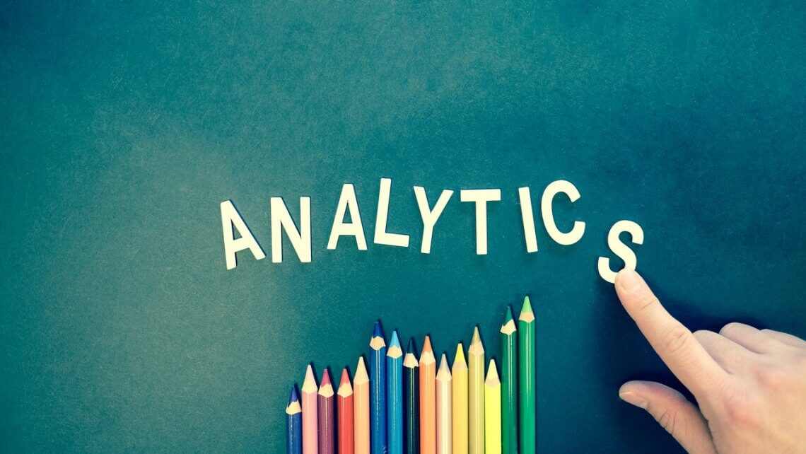 word analytics written on a green board with crayons underneath