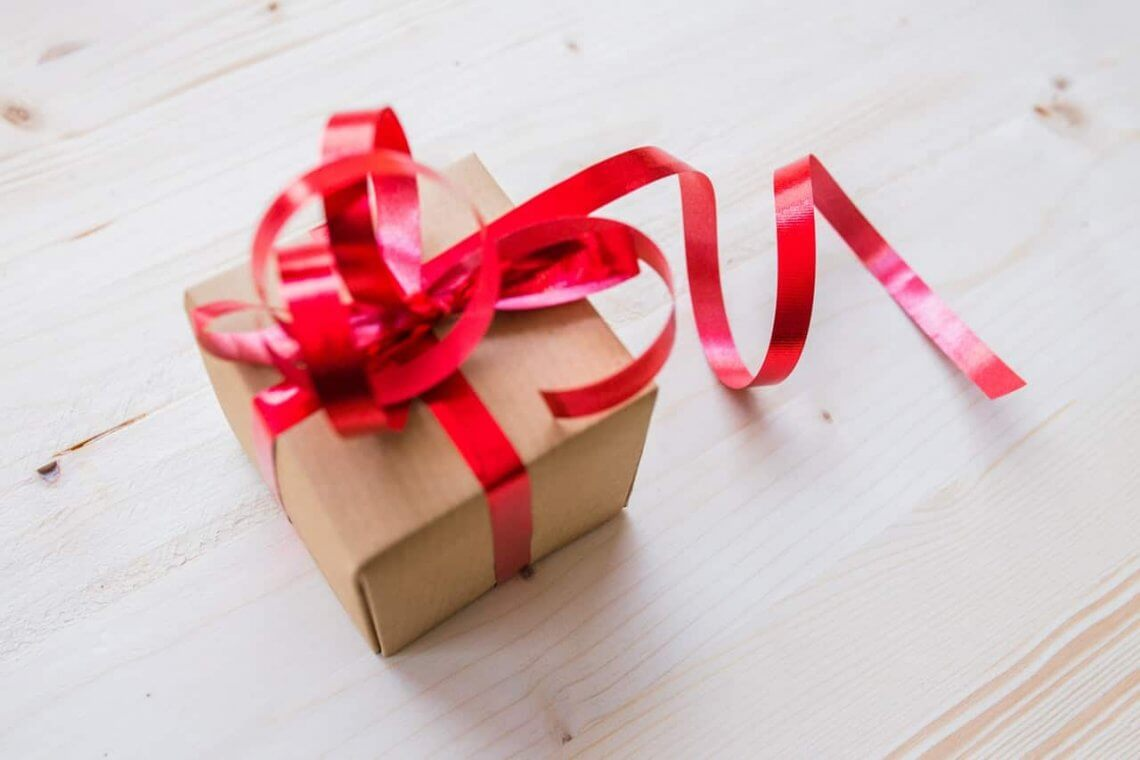 a gift in a box with red ribbon
