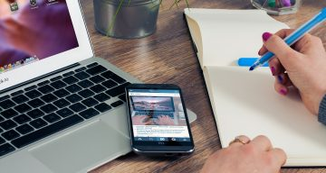 a view of a person hand writing in a notebook with laptop and smartphone on it