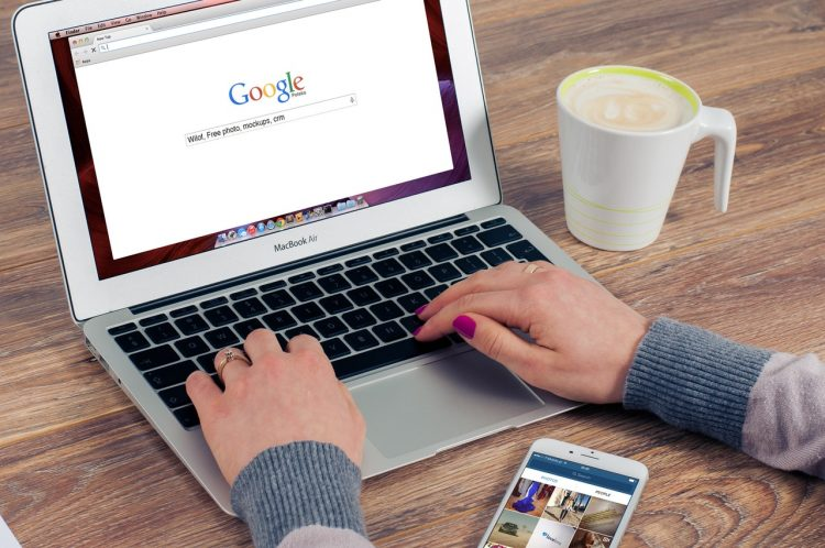 a women sitting in front of a computer with a coffee cup on the side and Google main page open