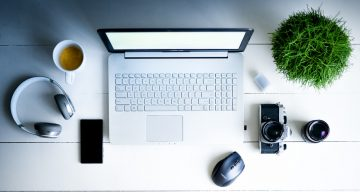 an aerial view of laptop, coffee, plant on a desk