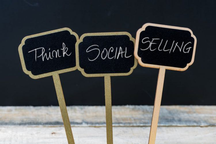 think social selling written with chalk on wooden mini blackboard labels, defocused chalkboard and wood table in background