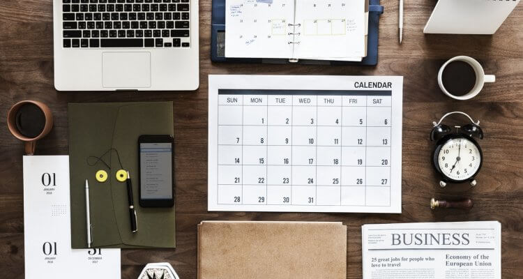 an aerial view of a desk with laptop, calendar, notebooks, clocks, coffee