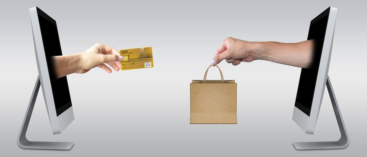 two hands emerging from computer screens, one holding a paper bag the other a credit card