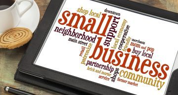 word cloud of terms related to small business on a tablet with coffee on left side