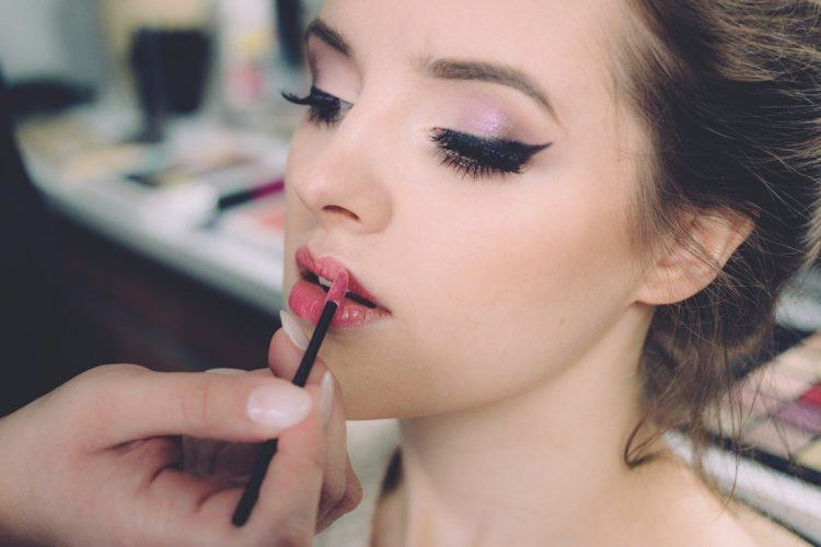 a woman have a makeup put on her