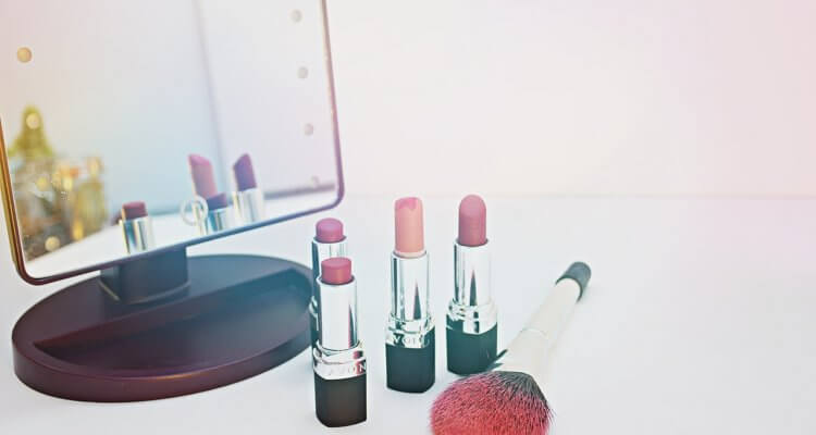 lipsticks on a table in front of a mirror