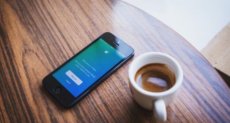 a smartphone with a login screen for Twitter lying on a wooden table with a espresso on the side