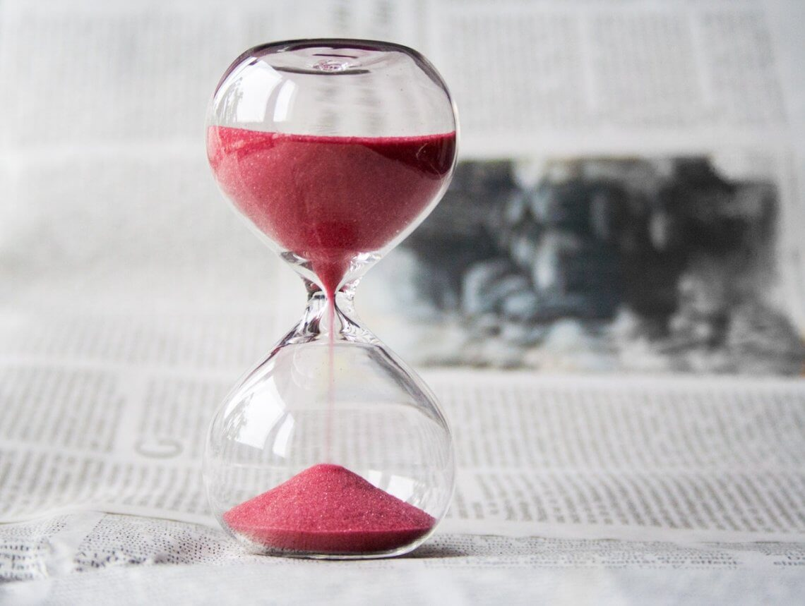 hourglass with pink sand on a white background