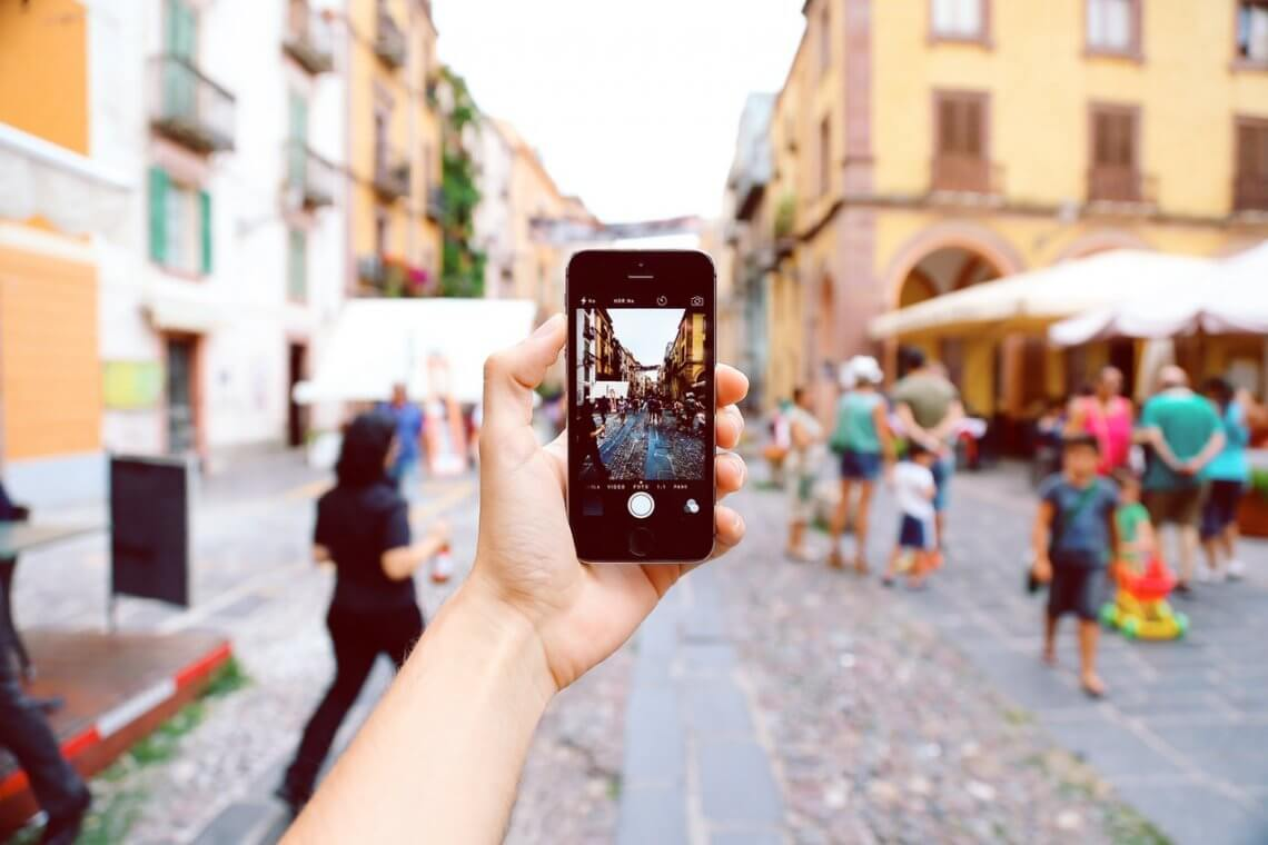 a person on a street holding a smartphone and taking a photo