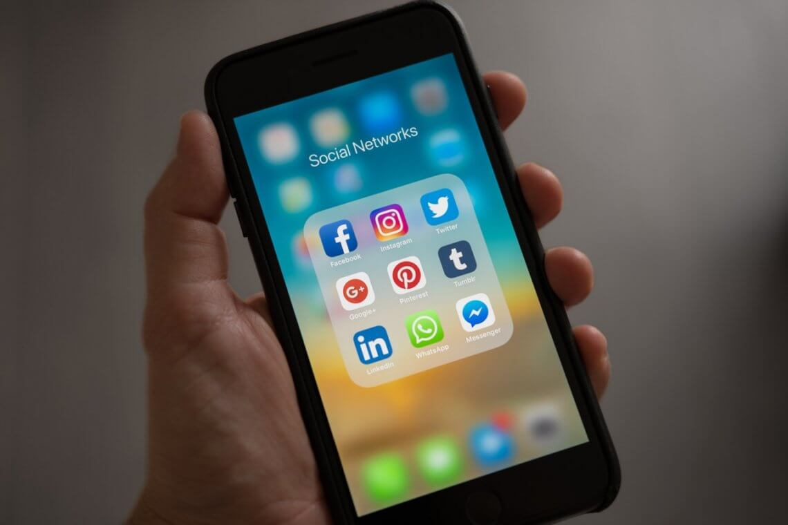 a person holding a smartphone with different social media apps on the screen