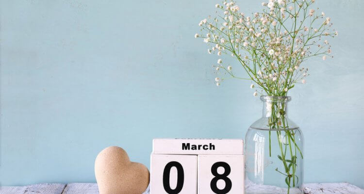 a table with flowers, wooden heart, and a calendar with a date 8th of March on a bleu background