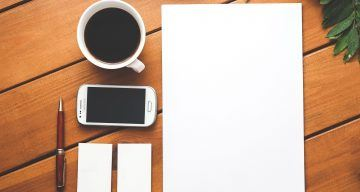 an aerial view of a desktop with a cup of coffee and a notepad
